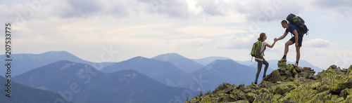 Young tourists with backpacks, athletic boy helps slim girl to clime rocky mountain top against bright summer sky and mountain range background Fototapeta