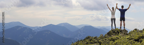 Fotografía  Panorama of young couple, athletic boy and slim girl standing with raised arms on rocky mountain top enjoying breathtaking summer mountain view
