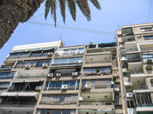 Old Apartment Building In Cairo, Egypt With Balconies, Air Conditioner Units And Satellite Dishes