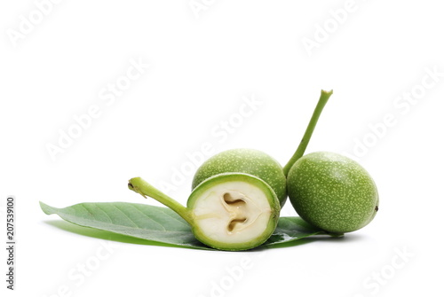 Fotografía  Half green walnut and leaf isolated on white background