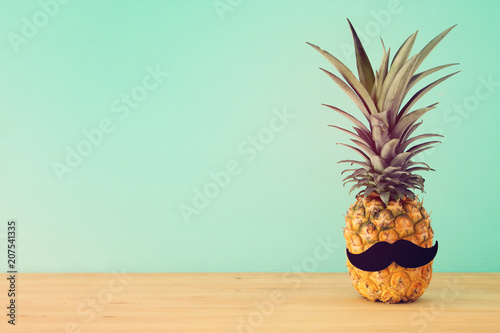 Pineapple on wooden table with funny moustache. Beach and tropical theme.