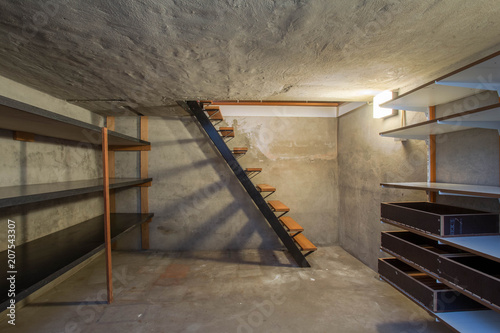 empty basement in abandoned old industrial building with little light and a wood Wallpaper Mural