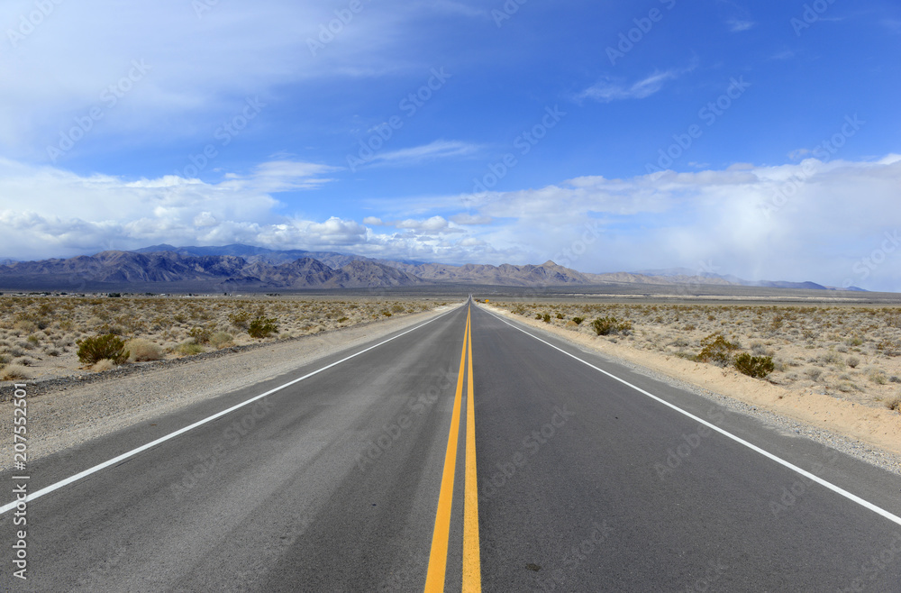 Fototapeta Driving on the open road in the desert with mountain backdrop