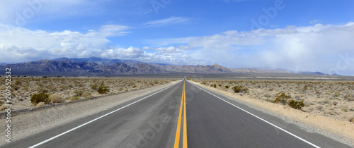 Fototapeta Driving on the open road in the desert with mountain backdrop obraz