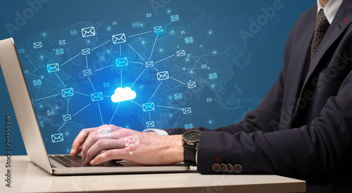 Fotografía Businessman hand sending a bunch of messages on laptop with cloud computing conc