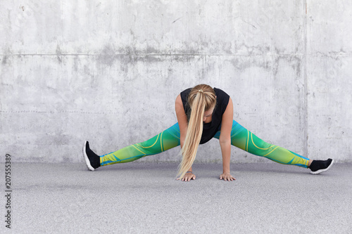 Active female in sports clothes, demonstrates her flexibility and