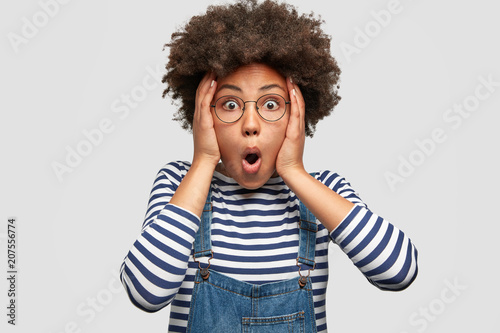 Photo Stunned African American female stares at camera and keeps mouth opened, scratches head and looks surprisingly, realizes bad news, stands against white background