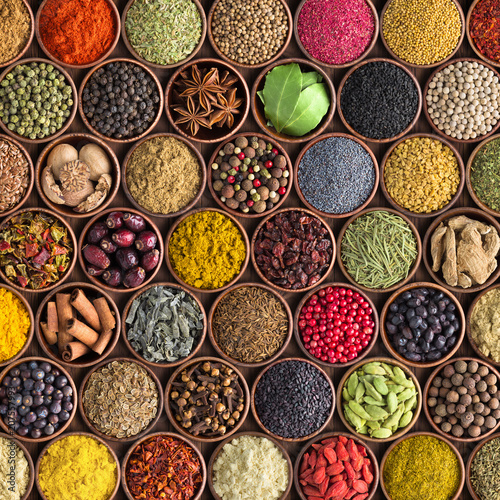 Colorful spices and herbs background. large set of seasonings in cups, top view