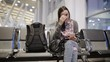 The woman at the airport in the waiting room with the phone waiting for departure