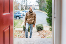 Young Man Standing On Front Porch Frontyard Steps In Front Of House Home Buyer Looking To Buy Property Real Estate Customer Client In Townhouse Residential Neighborhood, Cars Parked, Door Open