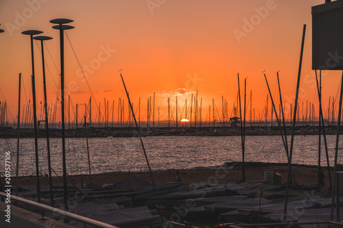Papiers peints Orange eclat Sunset over water behind boats and yachts at marina
