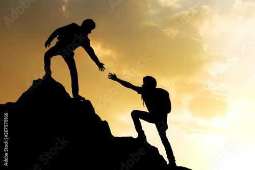 Fototapeta People helping on peak mountain and sunrise background climbing team work success business concept obraz