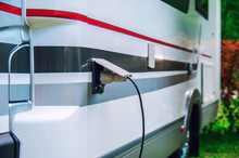Motorhome Stillife. Concept Of Power Supply Of The Camper. Plug Of The Electric Wire Is Inserted Into The Socket Of The Rv Trailer