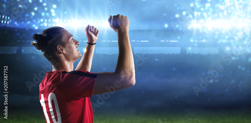 Happy soccer player with goal joy in the 3d imaginary stadium background
