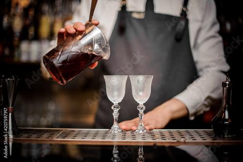 Fotografie, Obraz  Bartender pouring fresh summer Arnaud cocktail into the glasses