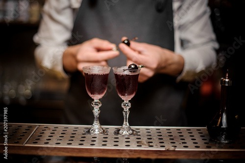 Barman decorating two glasses filled with strong summer Arnaud cocktail Canvas Print