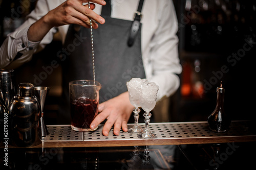 Photo Bartender stirring fresh alcoholic cocktail in glass