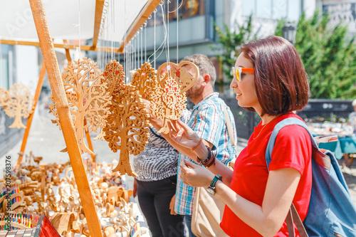 Carta da parati  A woman tourist at a souvenir fair choosing handmade decorative woodcarving gift