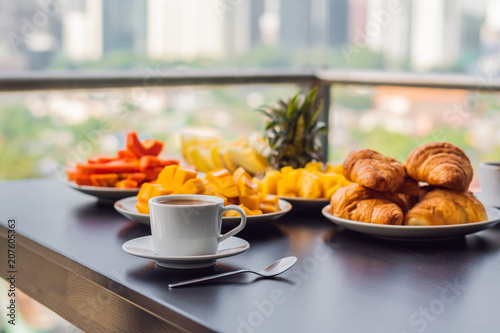 Photo  Breakfast table with coffee fruit and bread croisant on a balcony against the ba