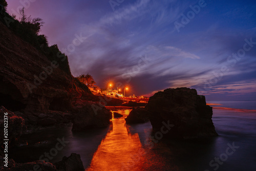 Photo  Sunset on the beach among the rocks near the city of Denia