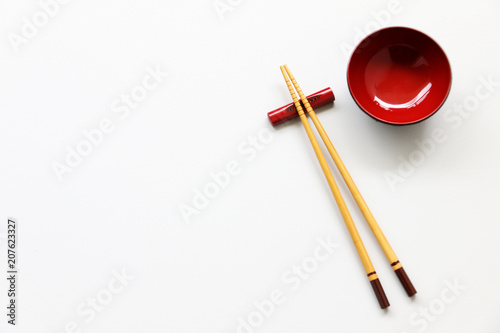 Foto  wood chopsticks and red bowl on White table background
