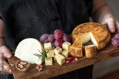 Photo sur Aluminium Assortiment cheese platter in hands of cheese maker