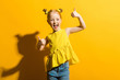 Leinwanddruck Bild - Girl with red hair on a yellow background. The girl laughs and shows the class sign.