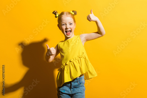 Photographie  Girl with red hair on a yellow background