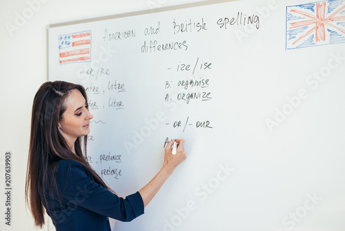 Fotografie, Obraz  Teacher explaining differences between American and British spelling writing on