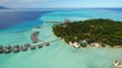 Aerial view of Motu Tautau, palm trees on little islets and turquoise water of blue lagoon, over water bungalows, tropical paradise of South Pacific Ocean - Tahaa island, seascape of French Polynesia