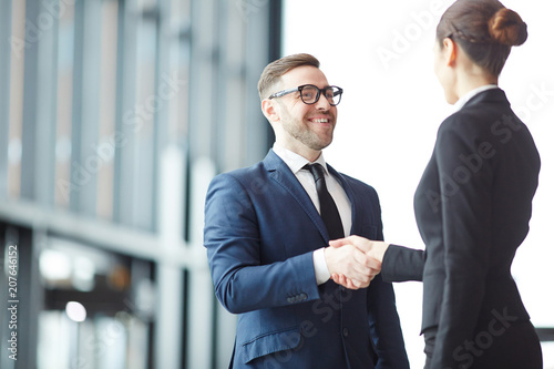 Happy young businessman greeting foreign colleague by handshake on arrival in ai Canvas Print