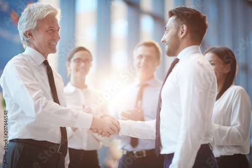 Cuadros en Lienzo Young and mature businessmen greeting one another by handshake with group of col