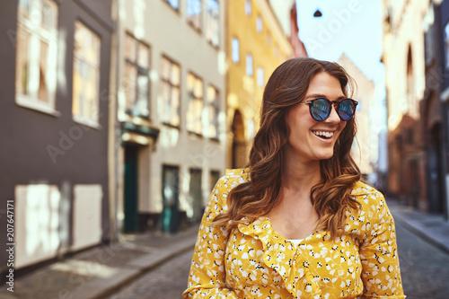 fototapeta na lodówkę Smiling young woman wearing sunglasses exploring city streets