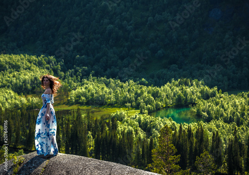 Poster Feeën en elfen Beautiful red hair woman girl feeling freedom and sexy enjoying the view of nature high above the mountains, sitting on a stone, summer forest outdoors wearing blue dress