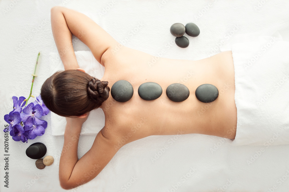 Fototapeta Stone treatment. Top view of beautiful young woman lying on front with spa stones on her back.  Beauty treatment concept.