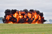 An Explosion At RAF Fairford During A Simulated Ground Attack. Orange Flames And Debris Can Be Seen Against Thick Black Smoke