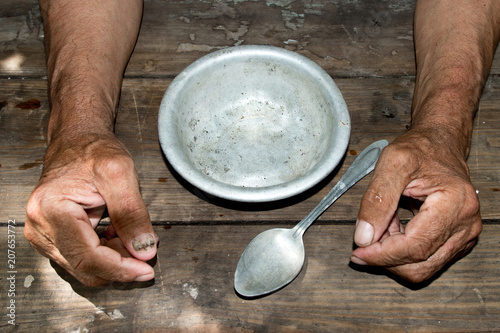 Foto hands the poor old man's and empty bowl on wood background
