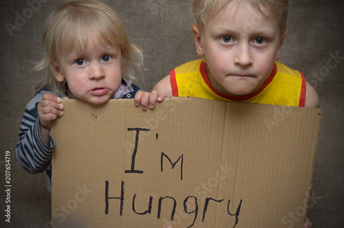 Fotografija  A hungry boy and a girl with a cardboard tablet with the inscription I'm hungry
