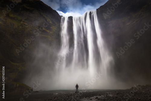 Skogafoss - May 04, 2018: Adventurer at the massive Skogafoss waterfall, Iceland - 207655306