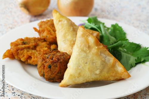 Selection of Indian samosas, onion bhajis and pakoras garnished with fresh coriander leaves