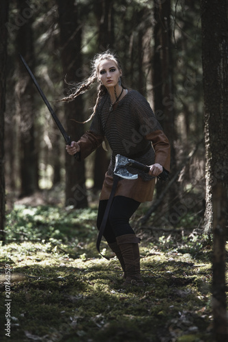 Plakát  Viking woman with sword and hammer wearing traditional warrior clothes in a deep mysterious forest