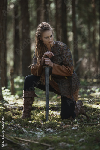 Plakát  Viking woman with sword wearing traditional warrior clothes in a deep mysterious forest