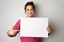 Pretty Smiling Woman Holding Empty Blank Board Isolated On The Gray Background
