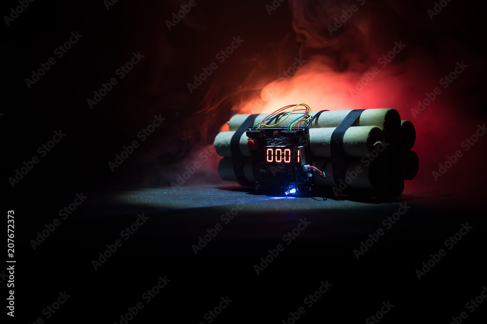 Fototapeta Image of a time bomb against dark background. Timer counting down to detonation illuminated in a shaft light shining through the darkness