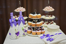 Wedding Decoration Elements, Festive Table With Cupcakes, Bottles Of Champagne With Blue Ribbons Of Silk, Candles And A Guest Book