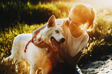 Portrait Of A Lovely Caucasian Woman Embracing Her Amazing Siberian White Husky Which Is Showing His Tongue Against Sunset.