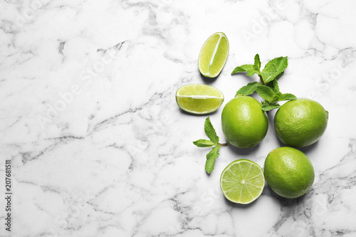 Fresh ripe limes on marble background, top view