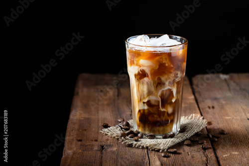 Photo  Ice coffee in a tall glass with cream poured over and coffee beans on a old rustic wooden table