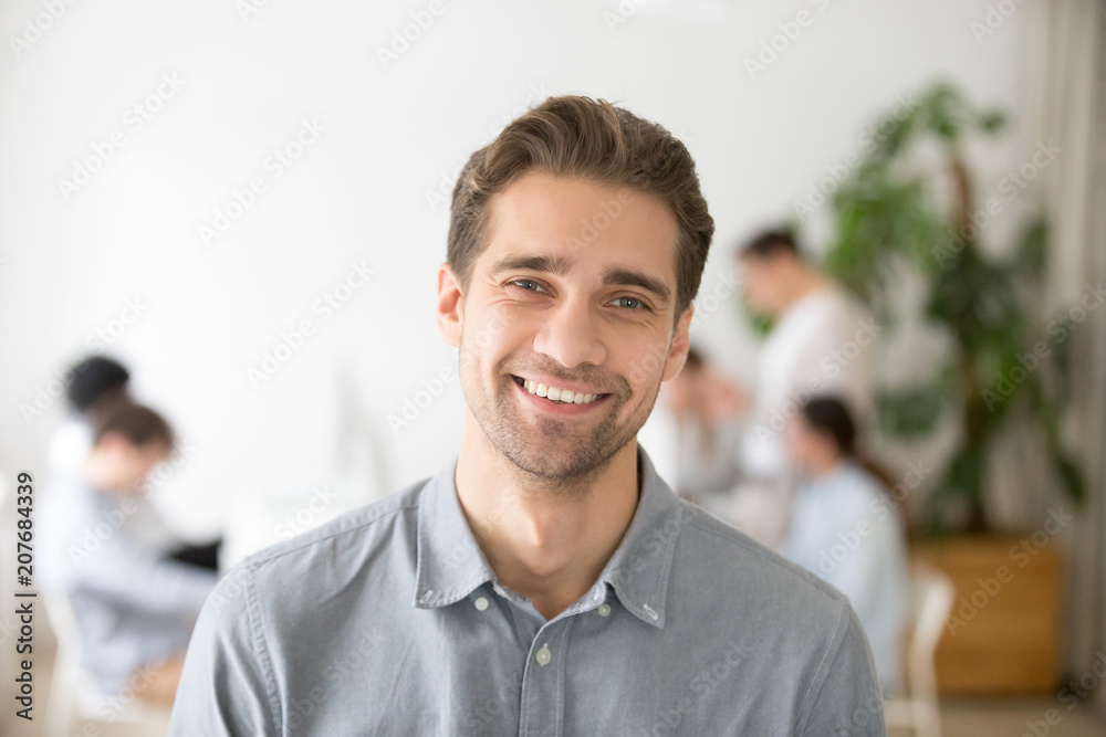 Fototapety, obrazy: Portrait of casual smiling Caucasian male worker laughing looking at camera, positive employee posing for company business catalogue with colleagues at background, having photo shoot in office