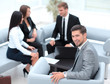 businessman sitting in an office on the background of business team.